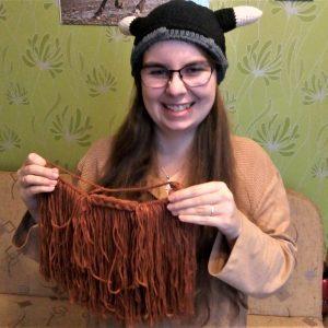 Dziewczyna trzymająca brodę wikinga zrobioną na drutach.