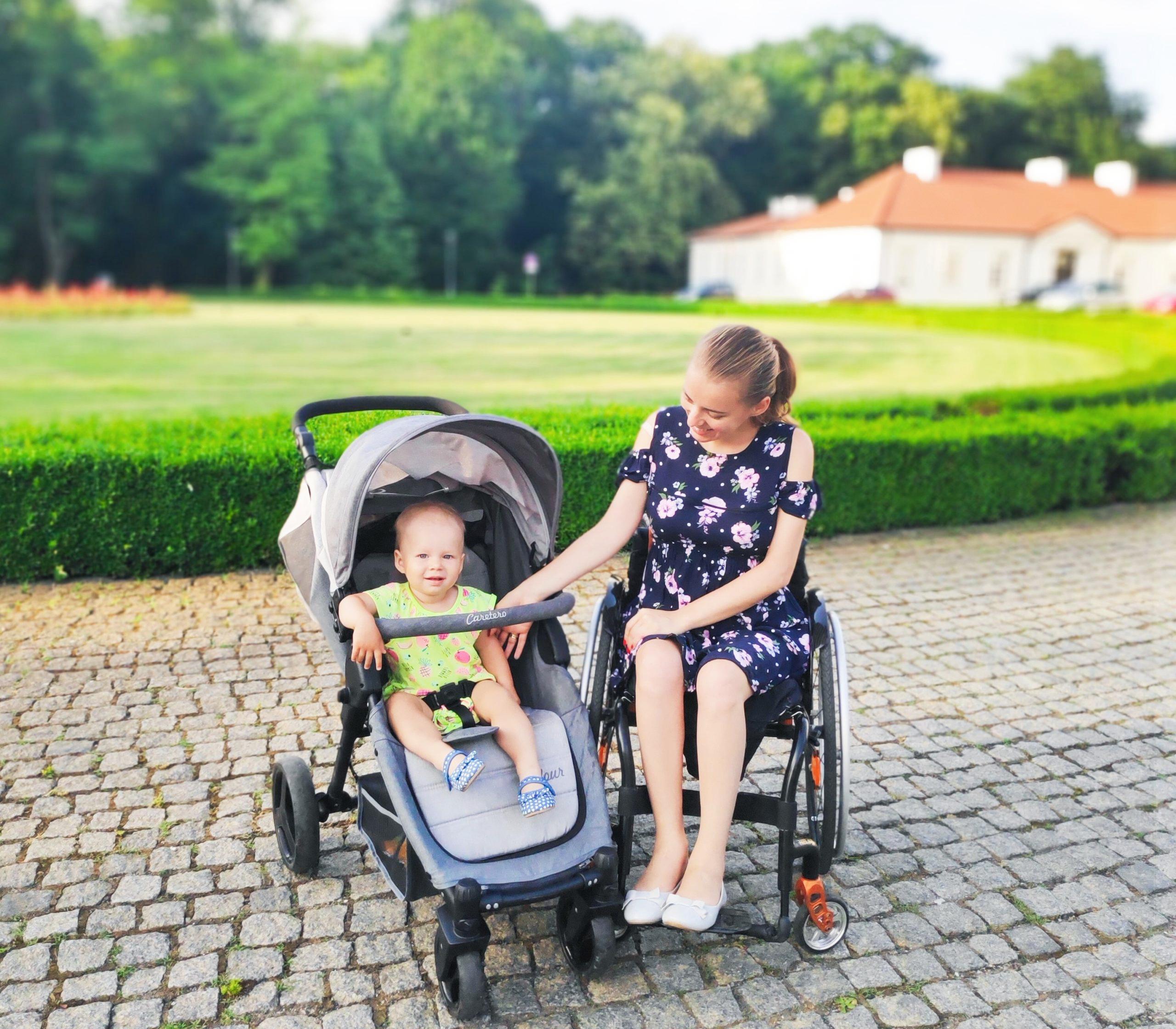 Mama na wózku, a obok niej małe dziecko w wózeczku.
