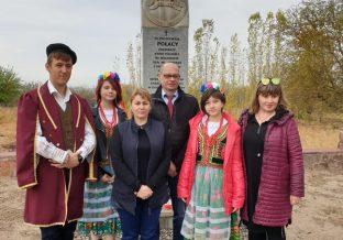 kobieta stoi w grupie koło pomnika
