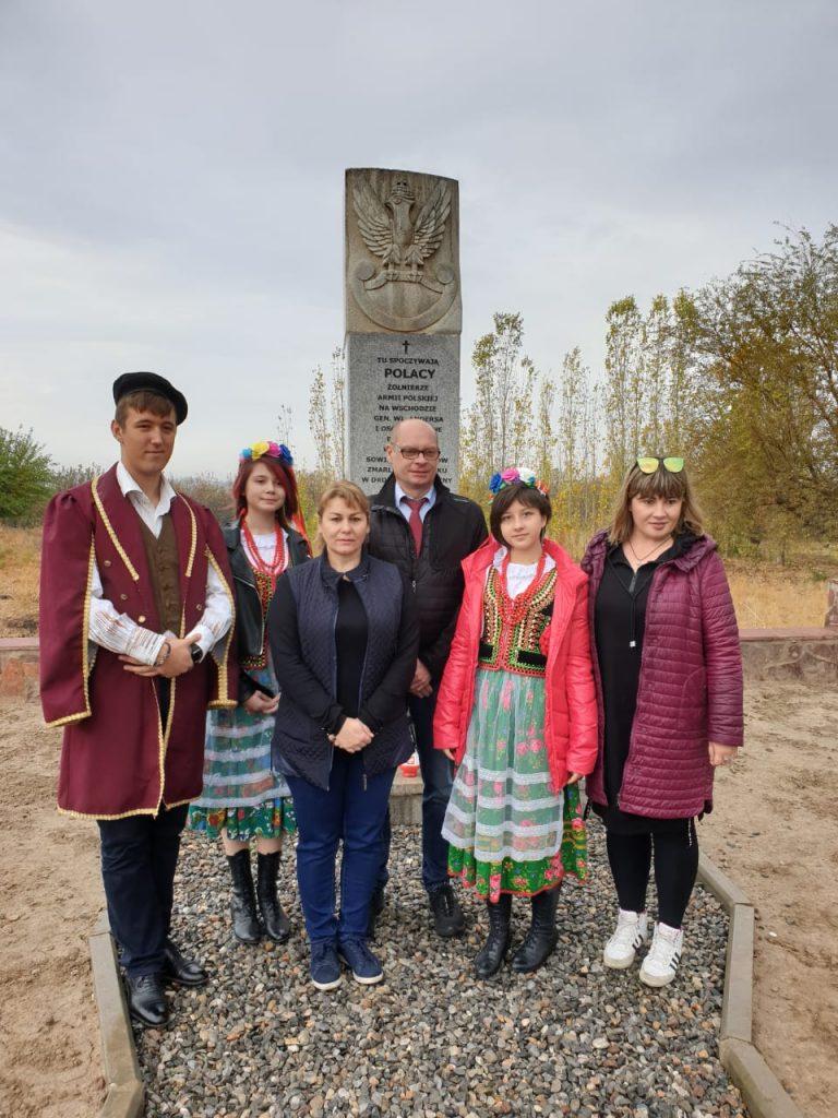 kobieta stoi wgrupie koło pomnika
