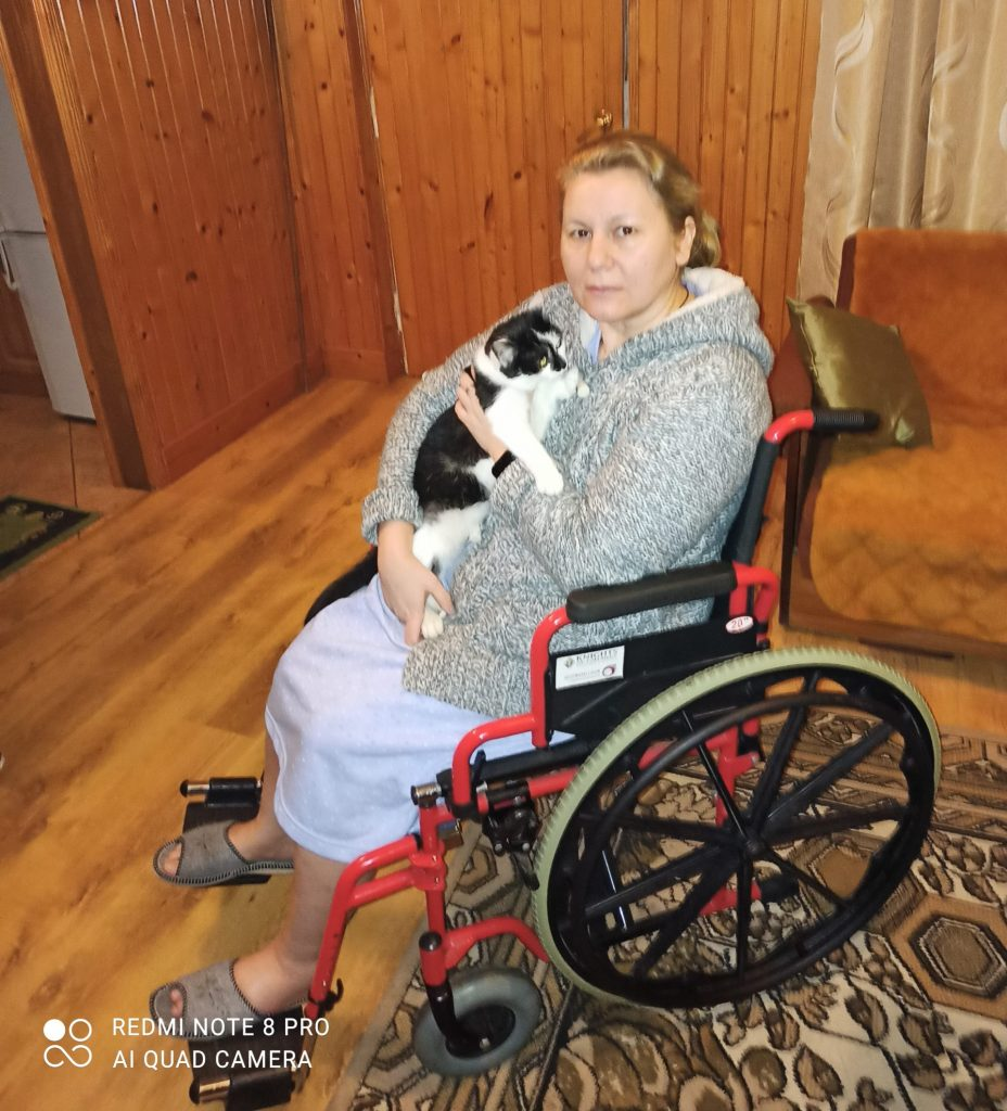 kobieta siedzi nawózku itrzyma kota narękach