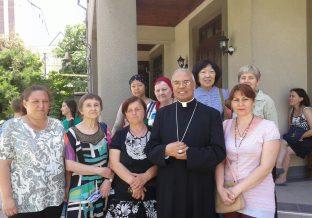 kobieta stoi z grupą koło księdza