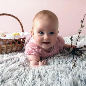 Uśmiechnięte niemowlę leży na futrzanym kocu. Trzyma w lewej ręce bazie. Obok dziecka wiklinowy koszyk wielkanocny.