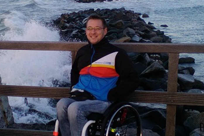 Chłopak w dresie na wózku, uśmiechnięty