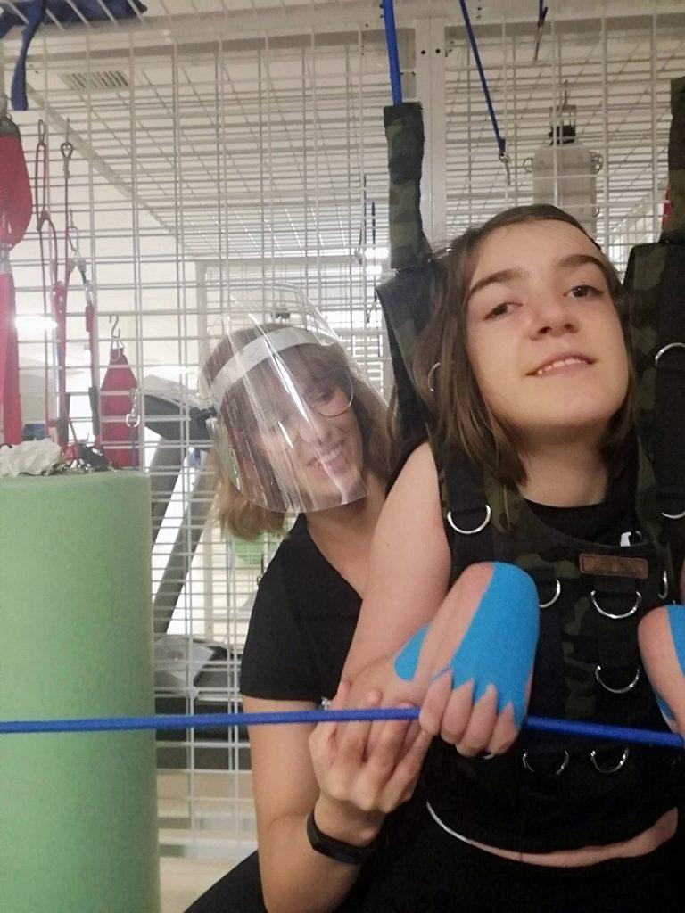 Dziewczynka narehabilitacji ruchowej ćwiczy