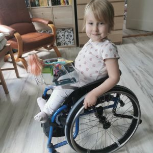 mała dziewczynka na wózku uśmiecha się